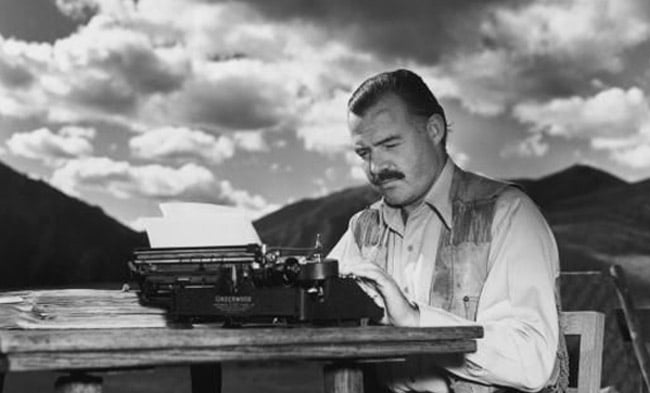ernest hemingway at desk writing typewriter outside