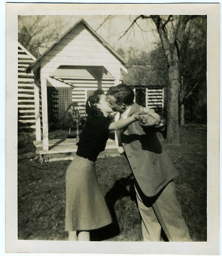 Vintage couple dancing and kissing in the yard.