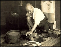 vintage older man in workshop sharpening tools