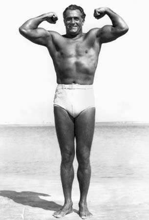 Vintage Charles Atlas giving muscle pose on beach.