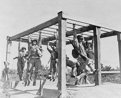 WWII soldiers doing military training on monkey bars.