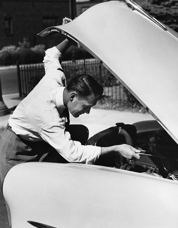 vintage man lifting hood of war working on engine