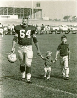 vintage football player walking off field with kids