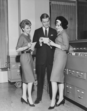 Vintage man speaking to women in office.