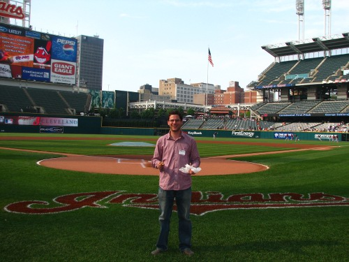 man standing on grass in cleveland indians baseball stadium