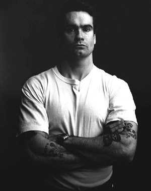 Muscular tattooed man in white shirt.