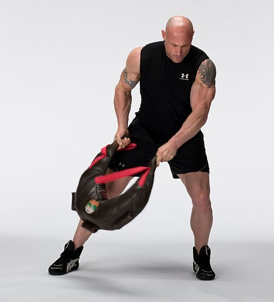 Strong man practicing with training bag.