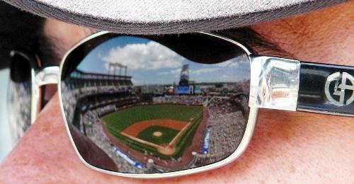 coors field rockies stadium reflected in man's sunglasses