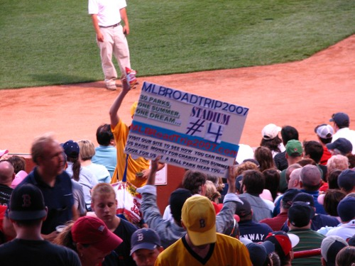 Man carrying MLB road trip board in  crowded stadium.