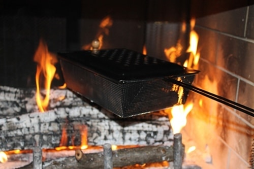 roasting nuts in chestnut cooker pan in fireplace