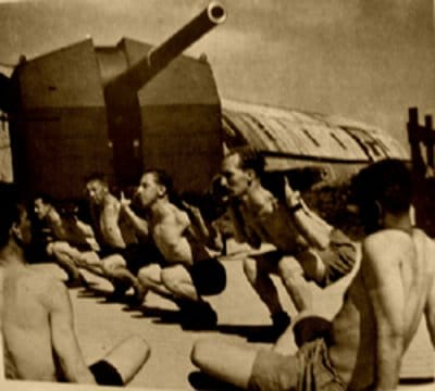 Vintage soldiers doing squats in front of tank ship.