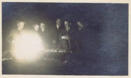 Vintage men sitting around campfire.