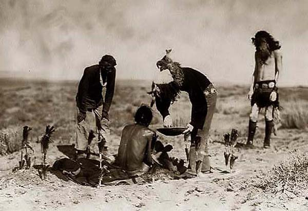 Vintage men organizing magic ceremony in field.