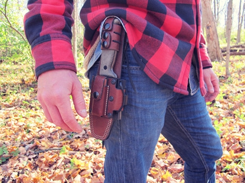 survival knife in leather holster on denim red flannel