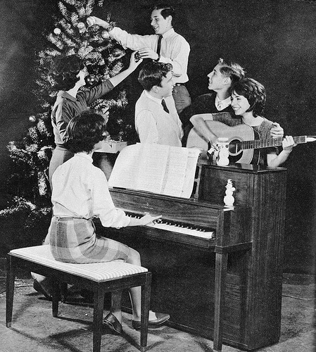 vintage family decorating christmas tree singing around piano