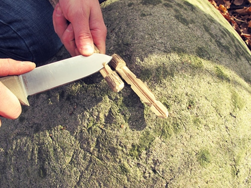 large survival knife cutting small sticks branches