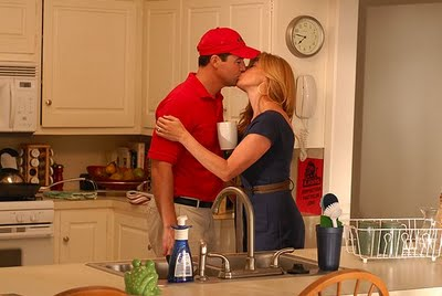 Taylor and Tami kissing in kitchen.