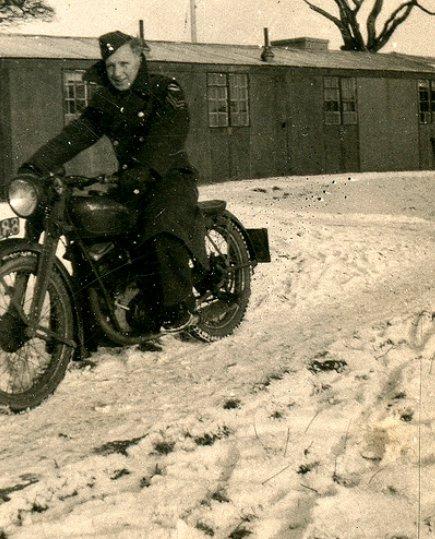Vintage man wearing overcoat on motorcycle in snow.