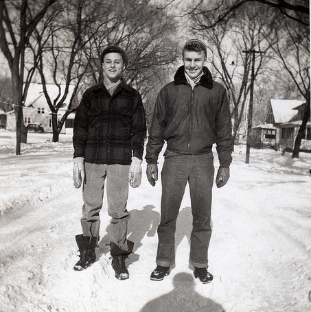 Vintage boys standing in a snowy road wearing coats, hats and gloves.