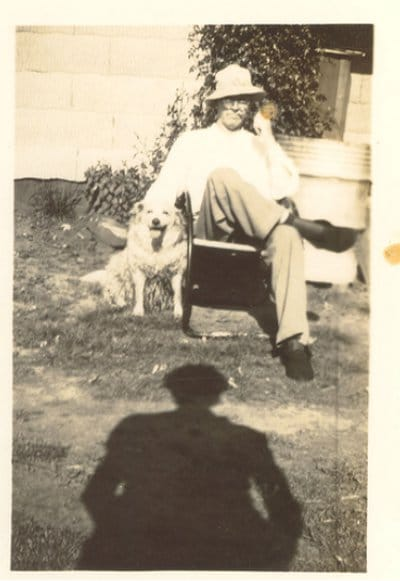 vintage man sitting in front yard with dog at side