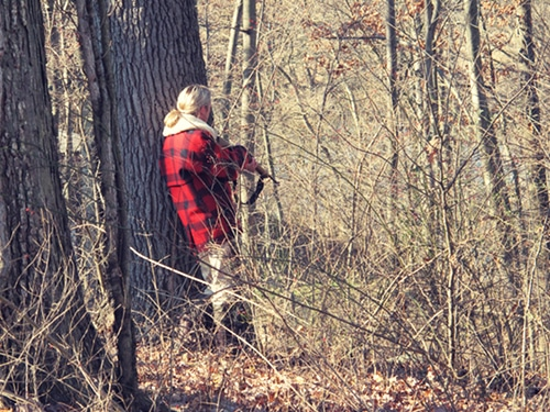 man hunting in woods with rifle red plaid