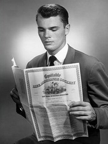 young man in suit reading over insurance paper