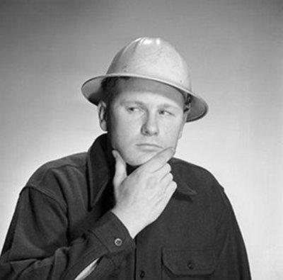 vintage man wearing hard hat rubbing chin