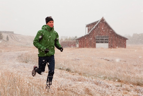Man in layers running through field while snowing.