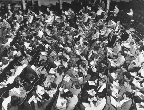 Vintage classroom full of students taking notes.