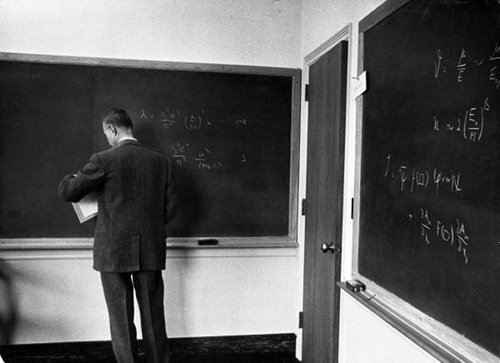 A man writing math equations on the blackboard.