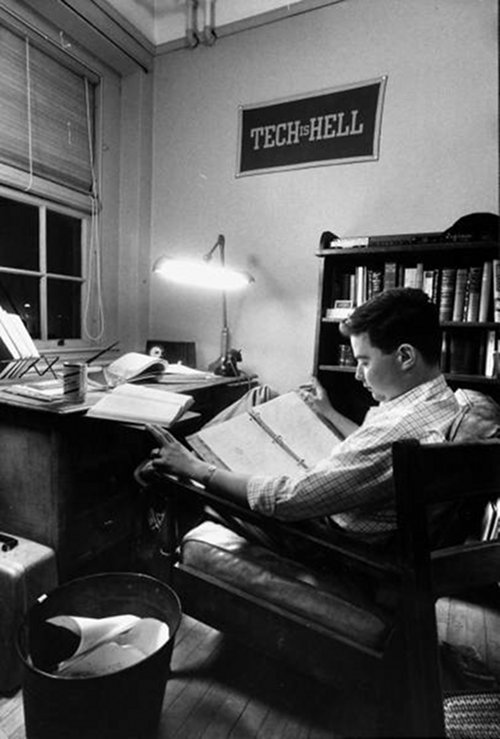 Vintage man studying in dorm room at desk in chair.