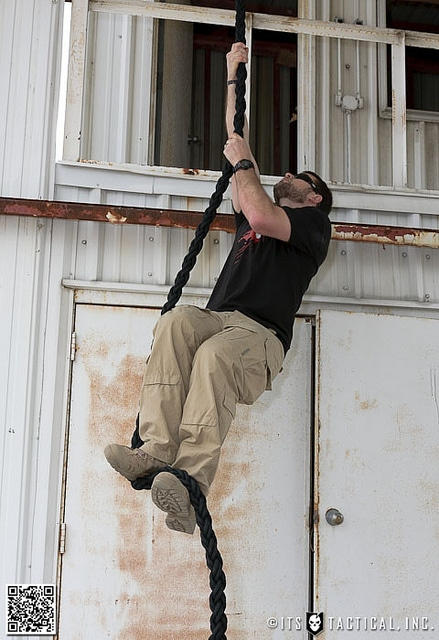 Man climbing a rope like a seal in warehouse.