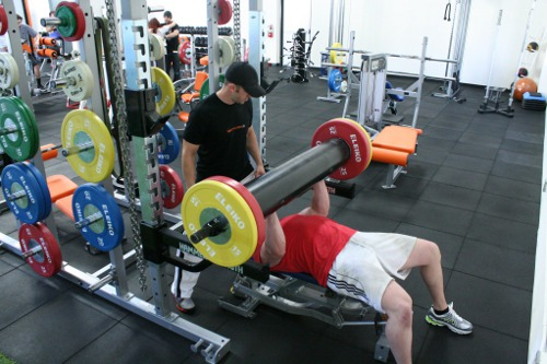 Ryan Martens lifting a weight while laying with a trainer.