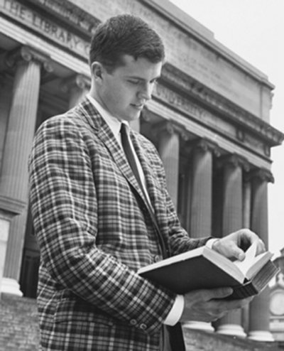vintage man in checkered blazer looking at book library