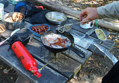 cooking bacon in portable camping stove outdoors