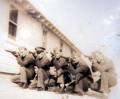 Vintage soldiers kneeling and aiming guns at unseen target.