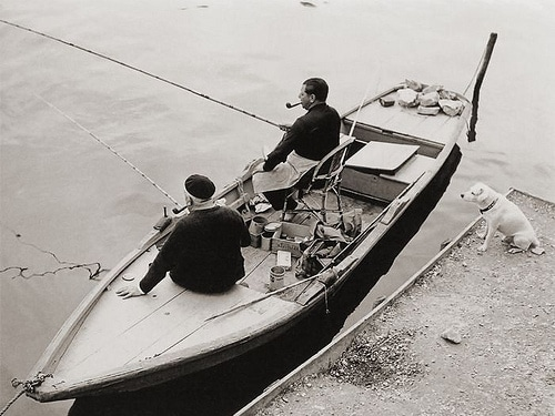 vintage men in fishing boat smoking pipes near dock