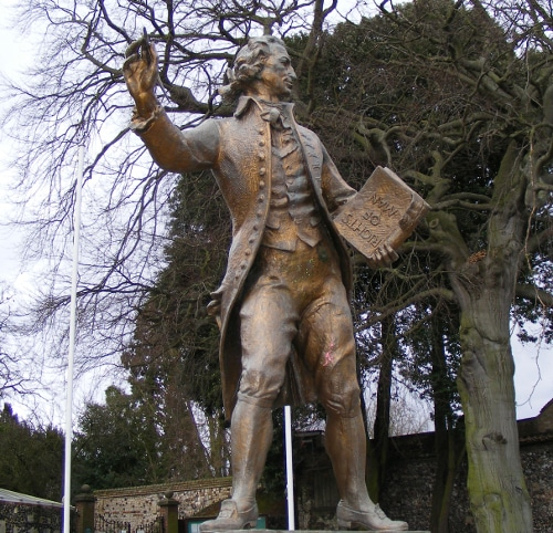 Thomas Paine bronze statue holding pen and book in hand.