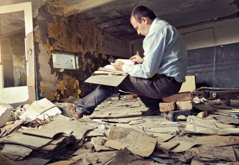 man in dilapidated room surrounded by papers