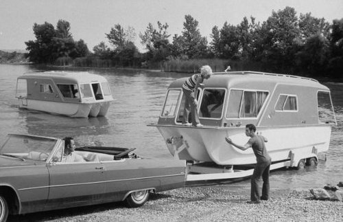 vintage family backing up trailer boat into water