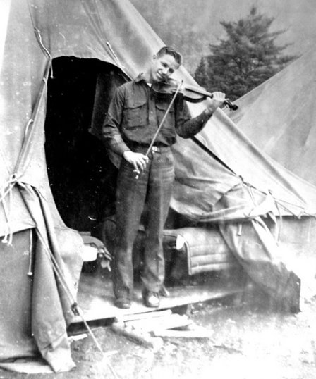 Vintage man playing violin outside of his tent.