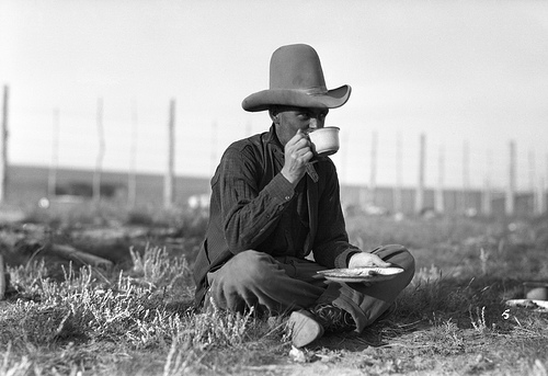 Vintage horse rider drinking tea in the field.