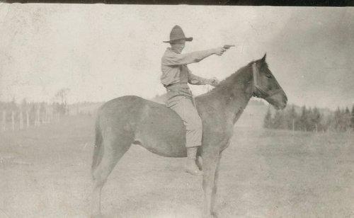Vintage horse rider shooting gun in forest.
