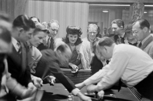 vintage casino crowd playing standing around craps table