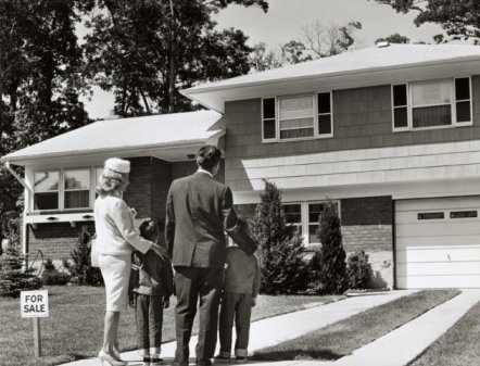 vintage family standing in front of new house for sale sign
