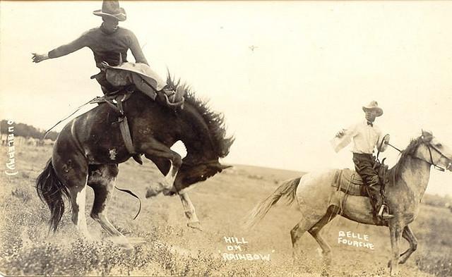 Vintage horsemen moving in open field.