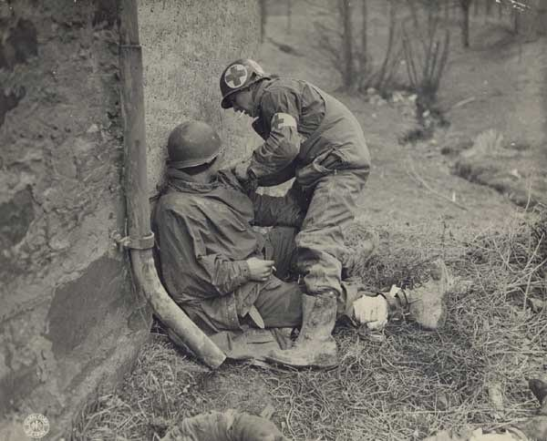 Vintage military medical officer making tourniquet in field.