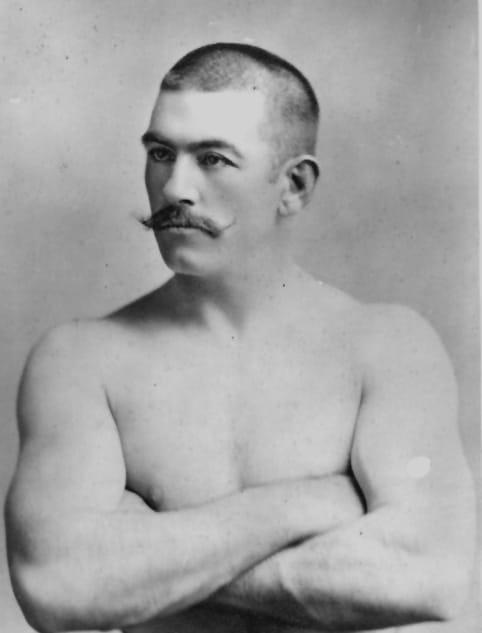 John l Sullivan give pose of mustache and chest portrait.