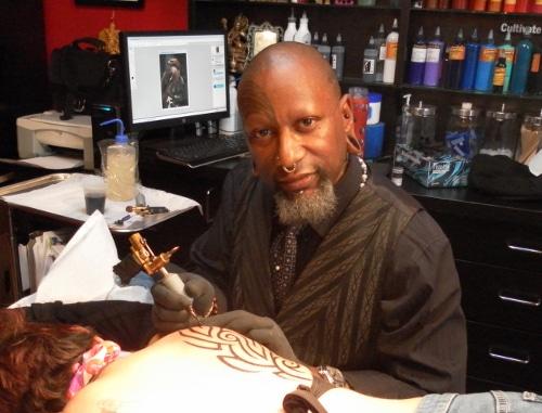 Zulu making tattoo on man's back.