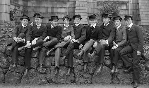 Group of guys posing on stone wall portrait.